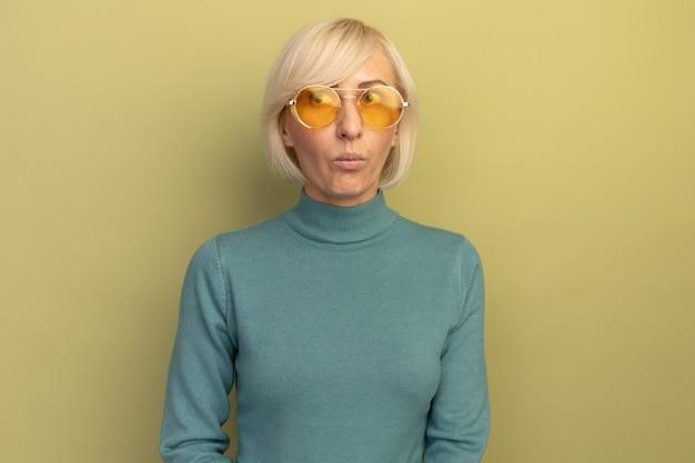 サングラスをかけた印象的なかなり金髪のスラブ女性はオリーブグリーンの側面を見る