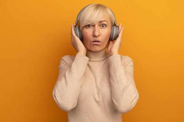 헤드폰에 감동 된 예쁜 금발의 슬라브 여자는 오렌지에 카메라를 본다