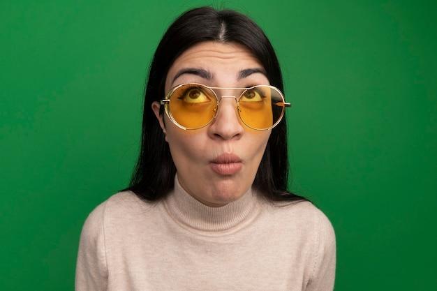 La ragazza caucasica del brunette graziosa impressionata in occhiali da sole osserva in su sul verde