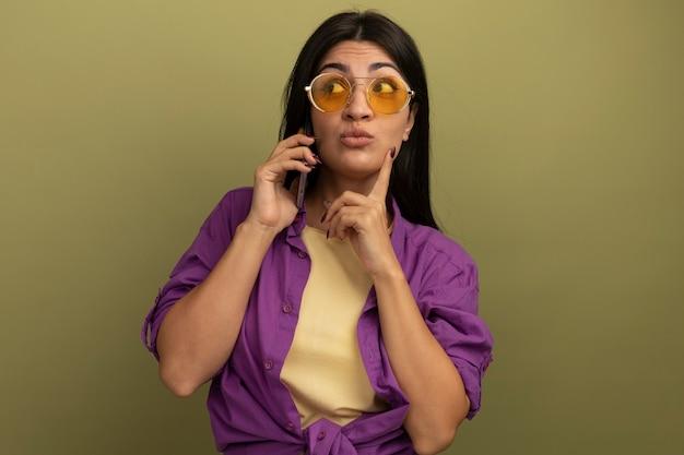 La ragazza caucasica bella mora colpita in occhiali da sole mette il dito sul mento guardando a lato e parlando al telefono su verde oliva