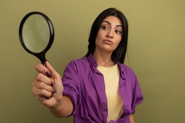Впечатленная симпатичная брюнетка женщина смотрит на увеличительное стекло, изолированное на оливково-зеленой стене