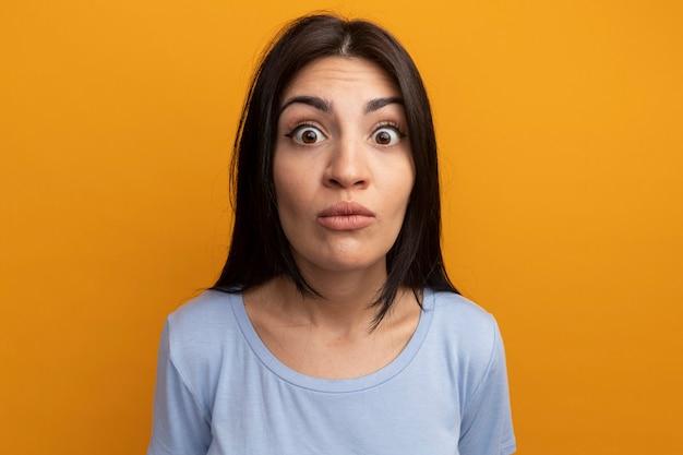 La donna graziosa impressionata del brunette esamina la parte anteriore isolata sulla parete arancione
