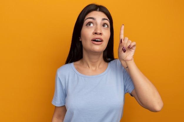 La donna graziosa del brunette impressionato osserva e indica in su isolato sulla parete arancione