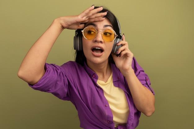 La donna graziosa del brunette impressionata in occhiali da sole con le cuffie tiene il palmo sulla fronte guardando il lato isolato sulla parete verde oliva