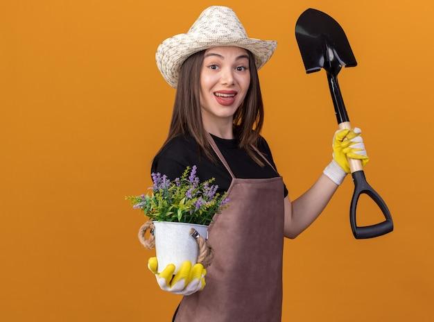 Impressionato giardiniere femmina caucasica che indossa cappello e guanti da giardinaggio si erge lateralmente tenendo vaso di fiori e vanga isolato sulla parete arancione con spazio di copia