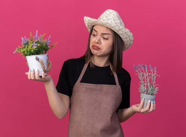 コピースペースでピンクの壁に隔離された植木鉢を保持し、見てガーデニング帽子をかぶっている印象的なかなり白人女性の庭師