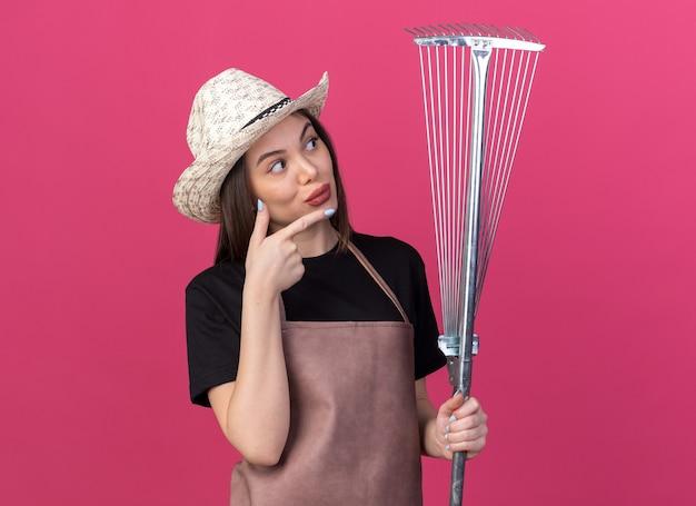 원예 모자를 쓰고 분홍색 잎 갈퀴를 가리키는 감동적인 예쁜 백인 여성 정원사