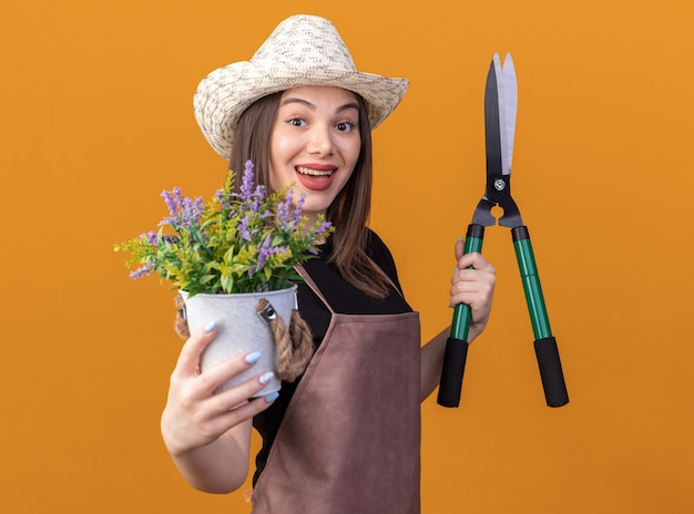 Впечатленная красивая кавказская женщина-садовник в садовой шляпе, держащая садовые ножницы и цветочный горшок