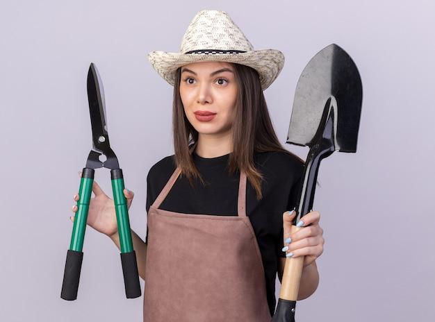 ガーデニングはさみとコピースペースで白い壁に隔離された側を見てスペードを保持しているガーデニング帽子をかぶっているかなり白人女性の庭師に感銘を受けました