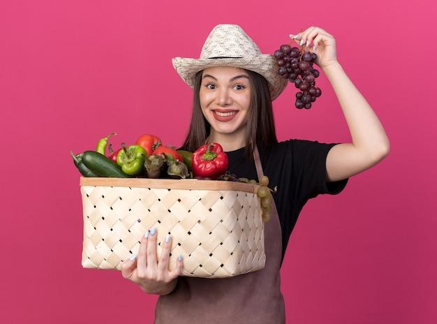 Впечатленная красивая кавказская женщина-садовник в садовой шляпе, держащая корзину с овощами и гроздь винограда