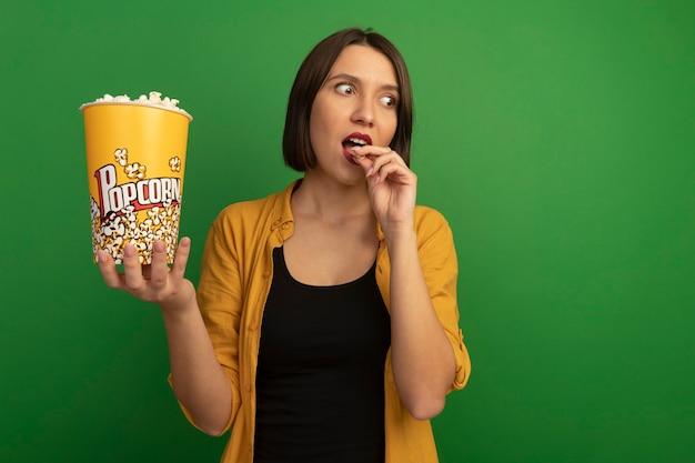 La donna abbastanza caucasica impressionata mangia e tiene il secchio di popcorn che esamina il lato isolato