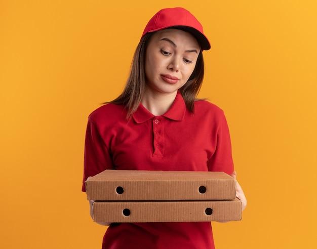 Впечатленная симпатичная доставщица в униформе держит и смотрит на коробки для пиццы, изолированные на оранжевой стене с копией пространства