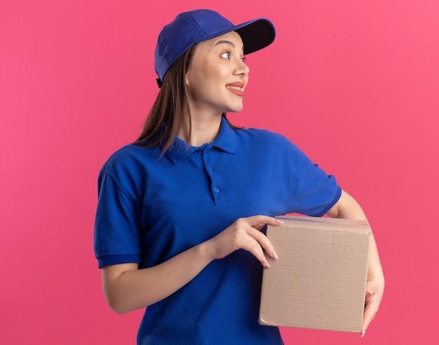 制服を着た感動の可愛い出産女性がカードボックスを持って横を見る