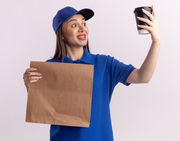 제복을 입은 예쁜 배달원은 종이 패키지를 들고 복사 공간이 있는 흰색 벽에 격리된 종이 컵을 봅니다.