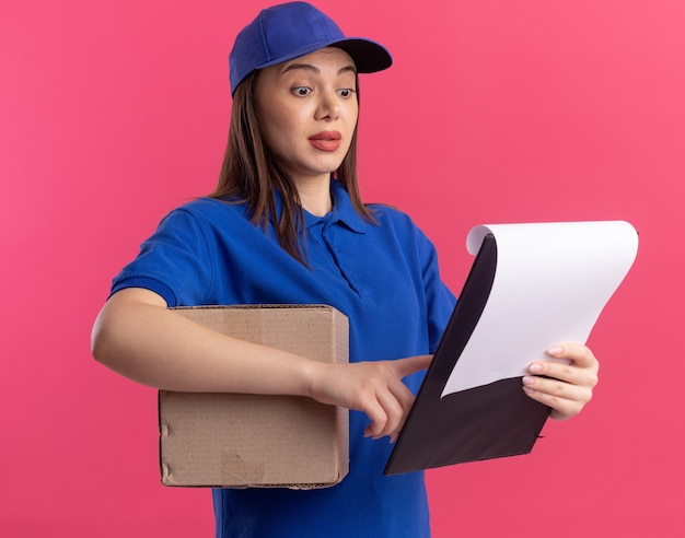 Impressionata donna graziosa delle consegne in uniforme che tiene in mano una scatola di cartone e guarda gli appunti isolati sulla parete rosa con spazio per le copie