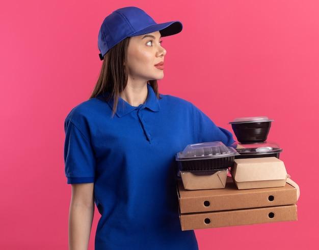 La donna graziosa di consegna impressionata in uniforme tiene il pacchetto ed i contenitori dell'alimento sulle scatole della pizza che guardano a lato sul colore rosa