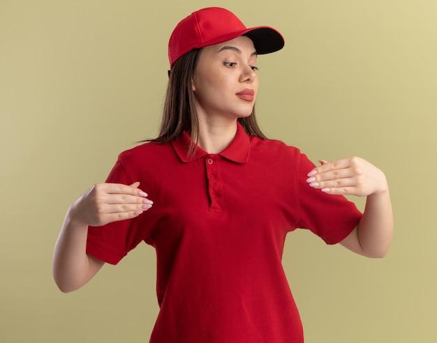 Impressionato donna graziosa di consegna in uniforme finge di tenere qualcosa e guarda a portata di mano su verde oliva