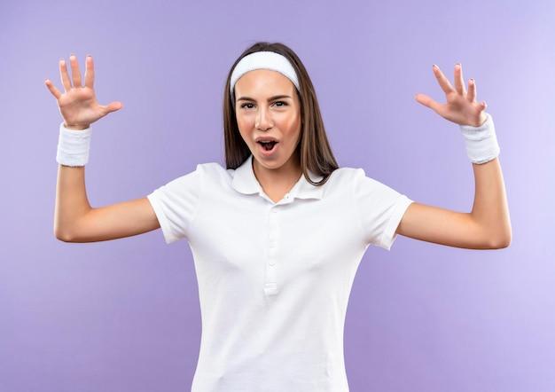 Impressionata ragazza piuttosto sportiva che indossa fascia e cinturino alzando le mani isolate sul muro viola