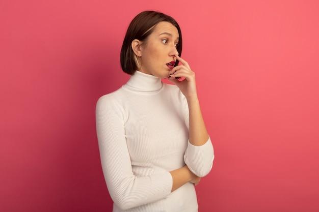 La donna graziosa impressionata tiene la mano vicino alla bocca che esamina il lato isolato sulla parete rosa