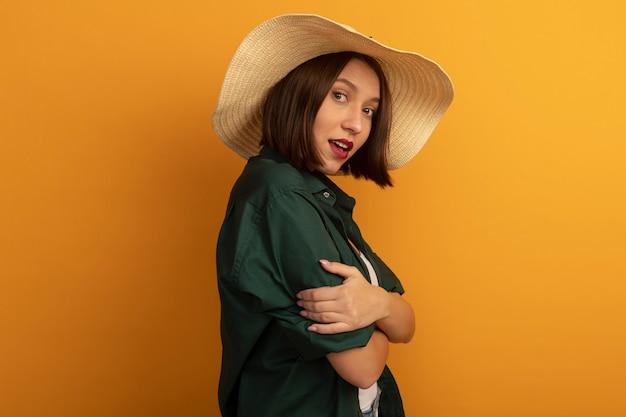 ビーチ帽子をかぶった感動きれいな女性は、オレンジ色の壁に分離された腕を持って横に立っています