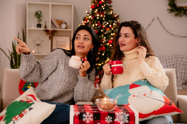 Impressionate ragazze carine tengono le tazze e guardano il lato seduto sulle poltrone e si godono il periodo natalizio a casa