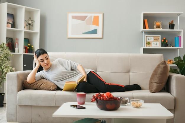 Impressionato mettendo la mano sulla testa giovane ragazza che legge un libro sdraiato sul divano dietro il tavolino nel soggiorno