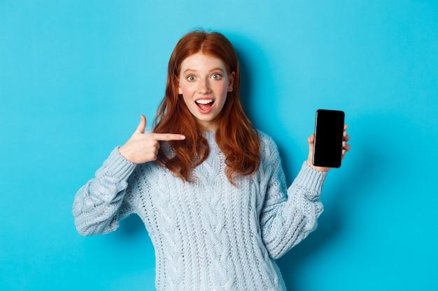 Впечатленная рыжая девушка, указывающая на экран телефона, показывающая приложение для смартфона или онлайн-предложение и возбужденная улыбка, стоящая в свитере на синем фоне.