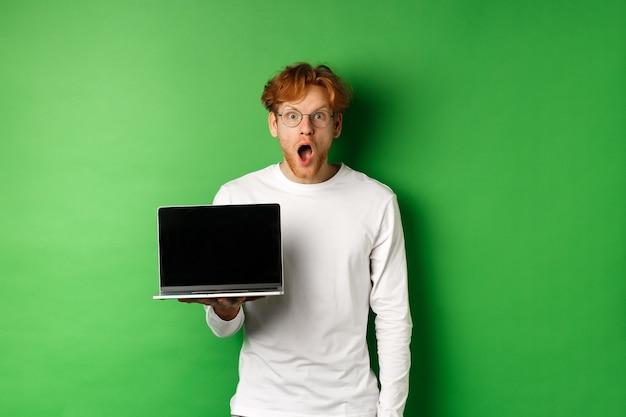온라인 프로모션을보고 노트북 화면을 표시하고 녹색 배경 위에 서서 불신으로 카메라를 응시 한 후 안경에 인상적인 빨간 머리 남자가 턱을 떨어 뜨립니다.