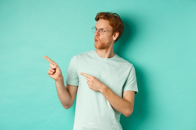 안경과 티셔츠에 감동적인 빨간 머리 남자, 손가락을 가리키고 프로모션 제안에서 왼쪽을보고, 청록색 배경 위에 서서 행복하게 쳐다보고 있습니다.