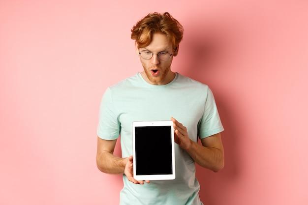 Впечатленный рыжий мужчина в очках показывает пустой экран цифрового планшета и с трепетом смотрит на дисплей ...