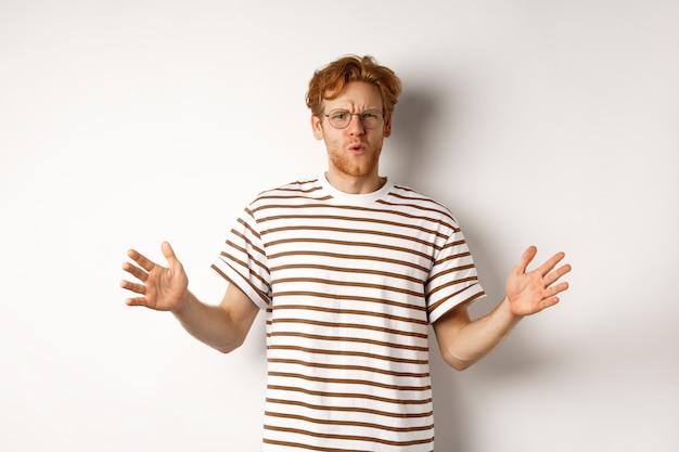 큰 무언가의 길이를 보여주는 안경에 감동 된 빨간 머리 남자는 큰 크기를 보여주고 흰색 배경 위에 서서 놀란 표정을 보여줍니다.
