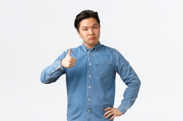 Impiegato maschio asiatico soddisfatto impressionato che mostra il pollice in su e guarda serio alla telecamera, lodando un buon lavoro, dicendo ben fatto o congratulazioni, soddisfatto del buon lavoro, in piedi sfondo bianco.
