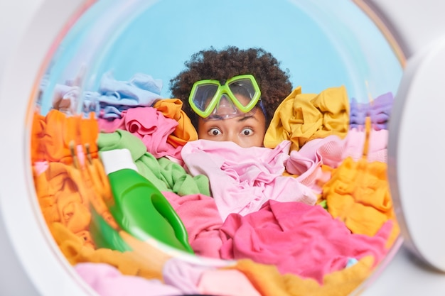 Impressed scared curly afro american woman does hard housework surrounded by big heap of laundry and bottle of detergent has washing time wears snorkeling mask pretends diving in sea at washer