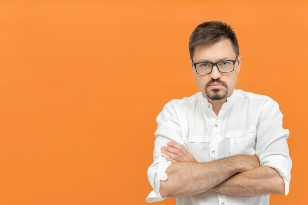 Not impressed. serious caucasian man feeling disappointed and displeased, looking at camera, annoyed and angry with crossed arms isolated on orange background. copy space.