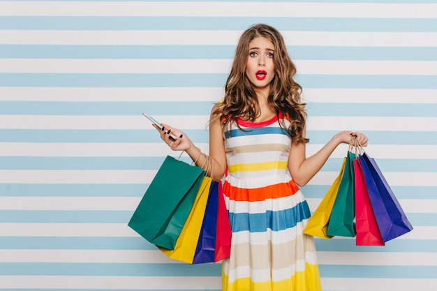 Impressed, shocked girl with shopping bag stopped talking on phone from what she saw at discount. female full-length photo on blue striped wall.