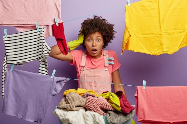 Впечатленная шокированная испуганная темнокожая женщина держит руку на голове, отвисла челюсть, перегруженная домашней работой