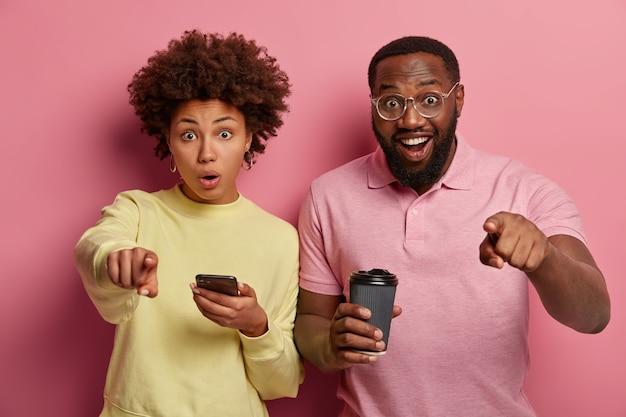 感動したショックを受けた女性と幸せな男がカメラを直接指さし、奇妙なことに気づき、携帯電話を使用し、持ち帰り用のコーヒーを飲み、唖然と感じる