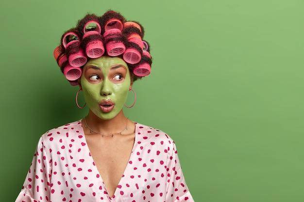 La donna colpita e scioccata applica una maschera all'argilla fresca per una pelle sana, esegue procedure di bellezza e trattamenti per il viso, indossa bigodini e vestaglia domestica, uno spazio vuoto sul muro verde.