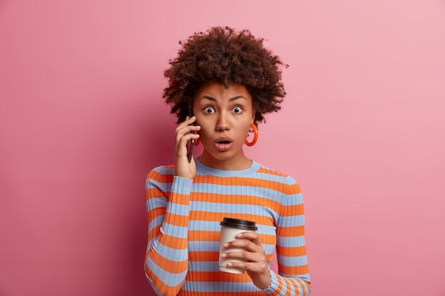 感動したショックを受けた女性は、新鮮な優れたニュースを聞き、電話で話し、驚きから口を開き、持ち帰り用のコーヒーを持ち、驚きを表現し、ピンクの壁に隔離されたカジュアルなストライプのジャンパーを着ています