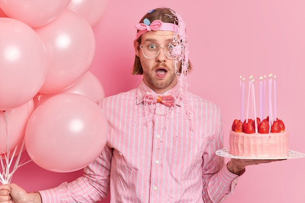 Impressed shocked young man in festive clothes stares bugged eyes keeps mouth opened receives unexpected congratulation from friend smeared with cream holds birthday cake and inflated balloons