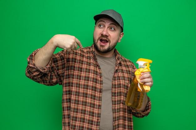 Impressionato uomo delle pulizie slavo che tiene in mano panni per la pulizia e detergente spray che punta a se stesso