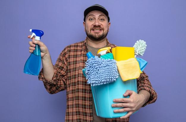 Uomo delle pulizie slavo impressionato che tiene in mano l'attrezzatura per la pulizia e il flacone spray