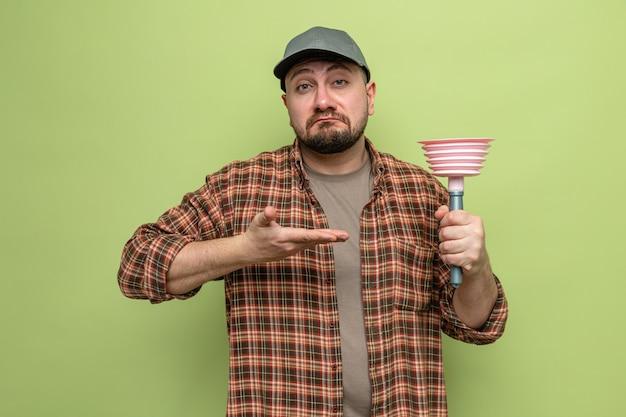 Impressionato uomo delle pulizie slavo che tiene e indica lo stantuffo di gomma