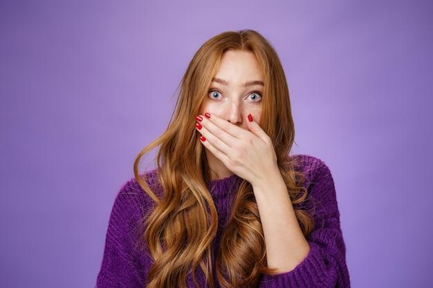 口を覆っている見事なゴシップを聞いて感動した言葉のないかわいい生姜の女の子は驚きを形成し、紫色の背景の上の予期しない啓示や噂に反応するように眉を上げて震えました。