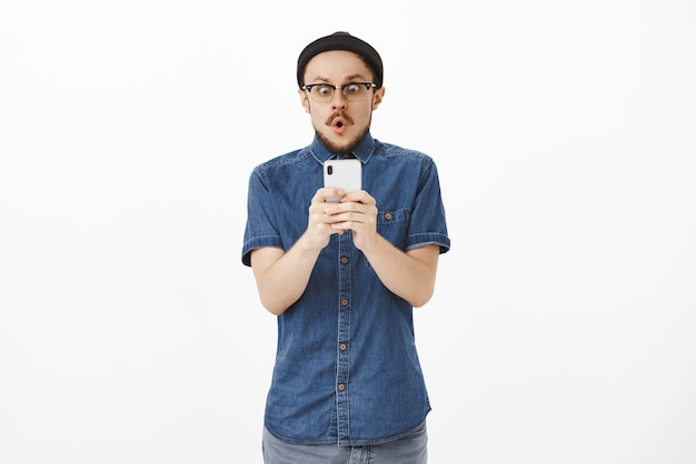 Impressed speechless excited and amazed handsome man with beard in glasses and beanie holding smartphone staring shocked at smartphone screen as if seeing awesome news folding lips with wow sound