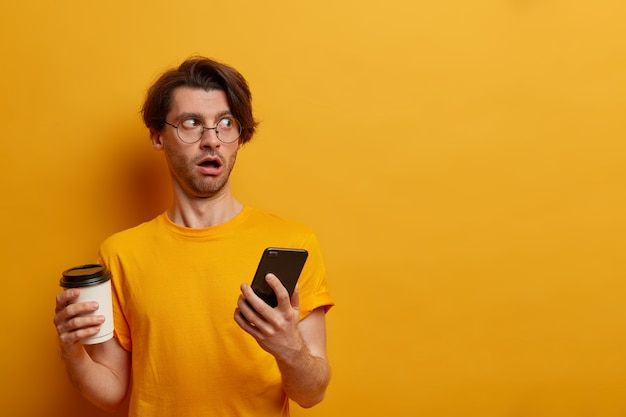 Impressed speechless guy looks aside with astounded expression, uses mobile phone and takeaway coffee, reads awesome news, chats with friend, wears round spectacles and yellow t shirt, blank space
