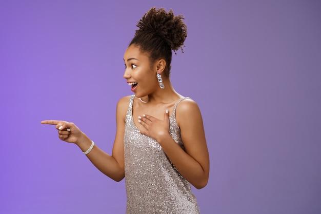 Впечатленная безмолвная, взволнованная элегантная молодая афро-американка видит, как знаменитость пресса ладони груди сердцебиение быстро указывает, глядя влево, удивлен, изумлен, стоя на синем фоне изумлен.