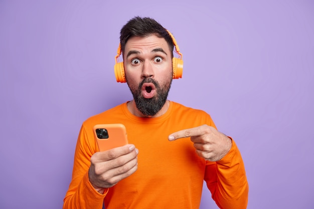 Impressed stunned man with thick beard indicates at smartphone display being amazed by stunning news wears headphones on ears wears bright clothes