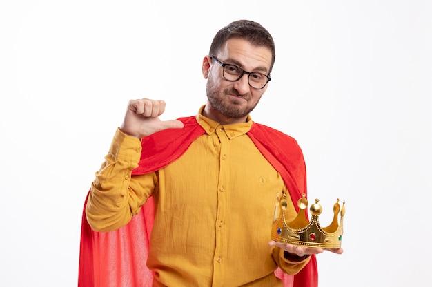 Impressionato supereroe uomo in vetri ottici con mantello rosso tiene e punti alla corona isolato sul muro bianco