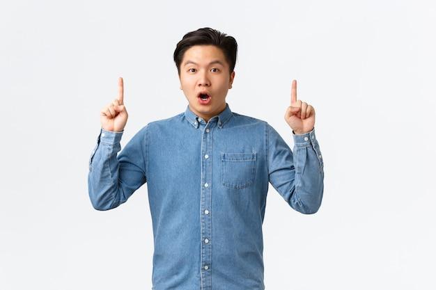 Uomo asiatico impressionato e sorpreso in camicia blu che discute di grandi notizie, puntando il dito verso l'alto stupito, guardando la telecamera stupito, trovando un collegamento interessante, condividendo con le persone, sfondo bianco.